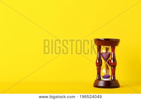 The Wooden hourglass on the yellow background