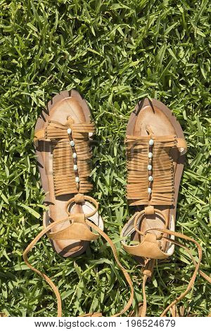 Woman's leather slippers on a green grass