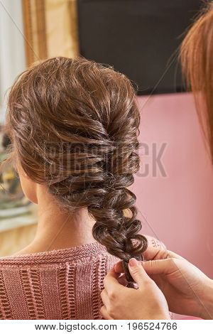 Hands of hairdresser plaiting braid. Female hairdo back view. Braid designs for women.