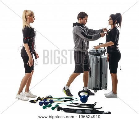 Trainer helps fitness women to set full electrical muscular stimulation suits. Various sport gear like kettlebells dumbbells belts and expanders around them. Studio photo isolated on white background.