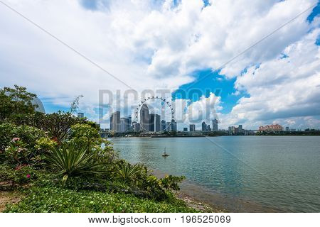 SINGAPORE - MARCH 22 2017: From the Gardens by the Bay Park picture of Singapore Flyer in a cloudy day in Singapore.