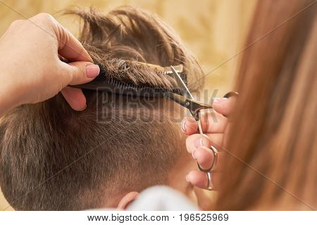 Hands of barber, scissors and comb. Guy getting haircut, close up.