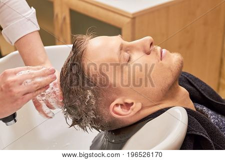 Hands of barber washing head. Male hair covered in shampoo. Best shampoo for men.