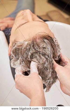 Hands washing hair with shampoo. Hair of barber shop customer. Professional shampoo brands.