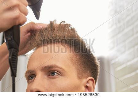 Barber drying hair, close up. Male hair and blow dryer.