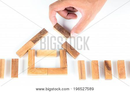 Man is moving wooden block stacking as house isolated on white background