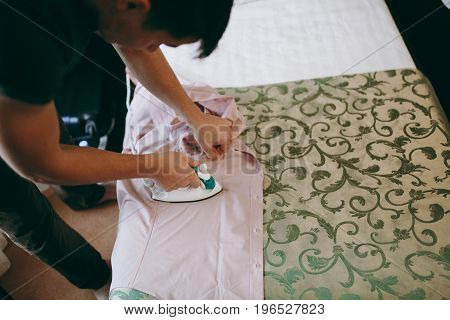 The Man Ironing The Shirt In Hotel