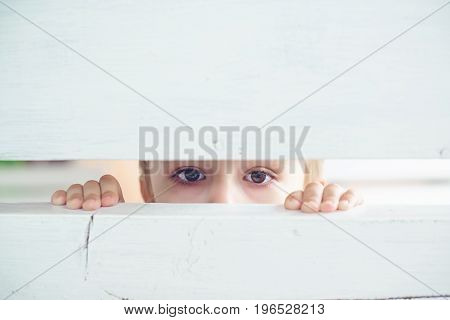 Sad Little Boy Looks Through The Fence Slit, View From Ambush.
