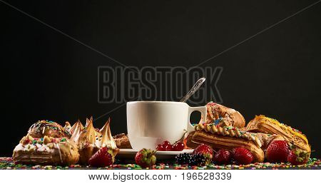 Delicious pastries with a cup of hot coffee. A colorful berry eclairs with strawberries blackberries currants on black table isolated on dark background with copy space