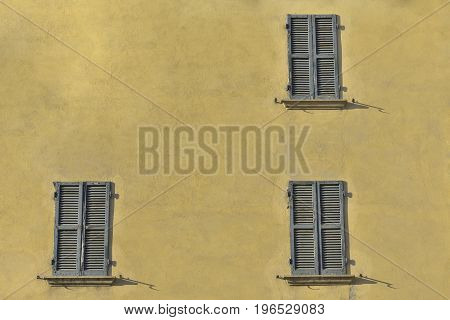 Closed green windows on yellow wall of old house in Florence city Italy