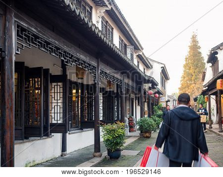 Suzhou, China - Nov 5, 2016: Shopping street at the historic Zhouzhuang Water Town. Numerous visitors can be seen walking along this path with shopping articles in hand.