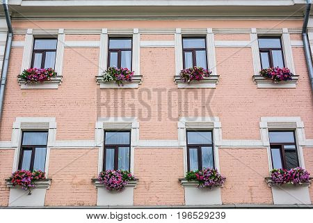 Old house facade with decorated flowers windows
