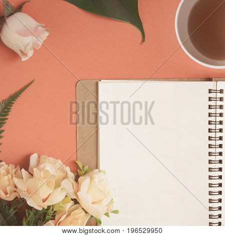 Flat Lay Notebook And Rose Placed On A Red Desk