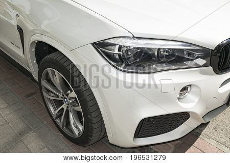 Sankt-Petersburg Russia July 21 2017 BMW X5 M Perfomance. Tire and alloy wheel. Headlight. Front view of a white modern luxury sport car. Car exterior details
