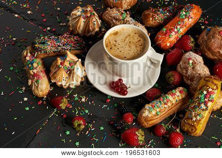 Bright and delicious fruit eclairs with currants strawberries blackberries served with a cup of coffee on dark stone background