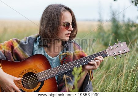 Beautiful Female With Short Hairstyle Wearing Stylish Sunglasses Resting Outdoors Playing Guitar Enj