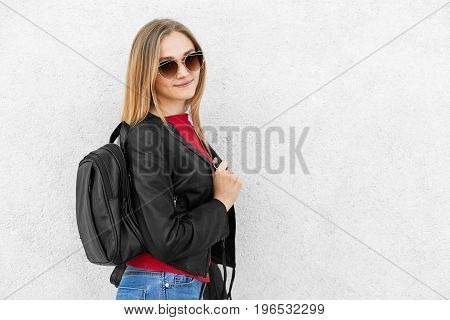 Young Female Wearing Leather Black Jacket, Trendy Sunglasses And Jeans Having Rucksack Posing Agains