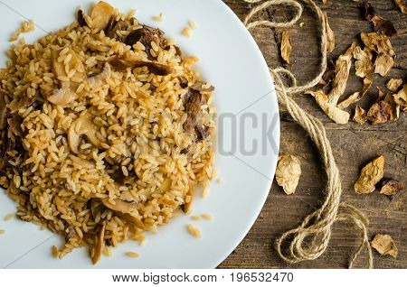 Homemade traditional Italian mushroom risotto on wooden table. Classic Risotto with mushrooms and vegetables served on a white plate. Wild mushrooms risotto. Top view.