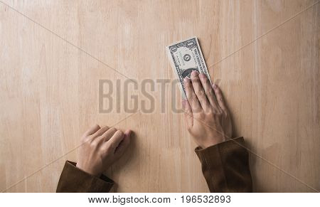 businessman hand giving dollar money on wooden table. concept offer money finance.