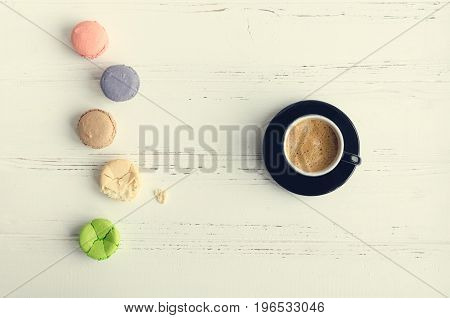 A cup of coffee and colorful almond cookies macaroon on white rustic wooden table. Breakfast on Mothers day Valentines Day or Womens day. Spring morning concept. Top view.