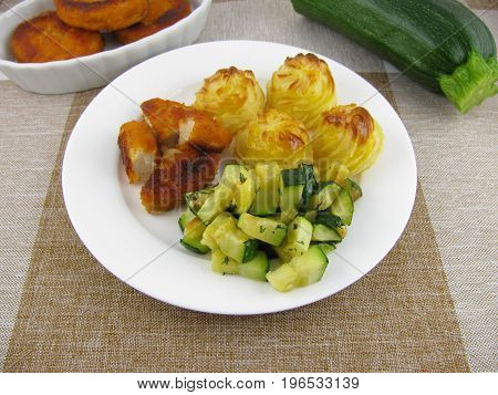 Duchess potatoes with chicken nuggets and fried zucchini