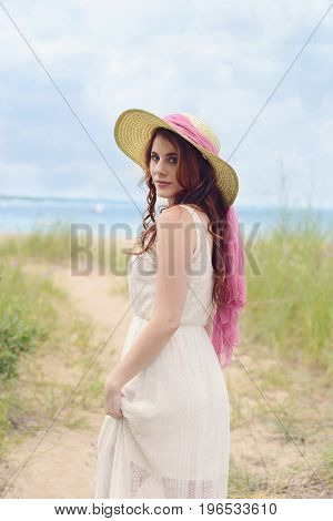 redhead woman with hat on beach path