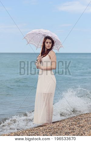 portrait of woman with umbrella at the beach