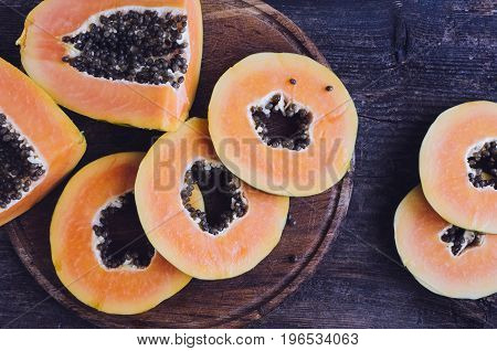 Slices of ripe sweet papaya on old wooden background. Top view.