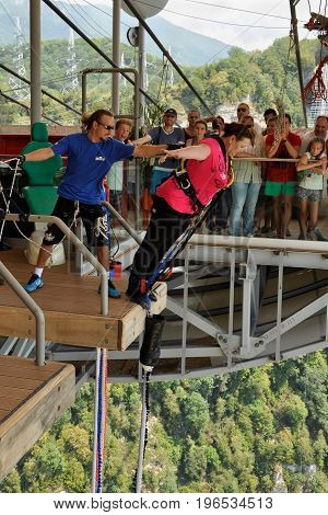 Russia Sochi Skypark - August 16 2014: A middle-aged woman jumping with bungee jump from a height of 69 metres from a special platform which is located at the bridge Skybridge
