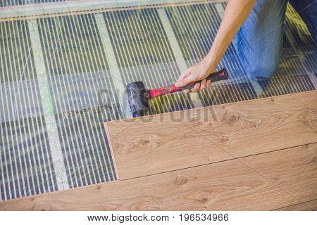 Man Installing New Wooden Laminate Flooring. Infrared Floor Heating System Under Laminate Floor