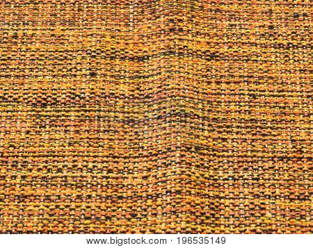 Rude cotton fabric in close-up, with ripple, mixed with yellow, black and orange.