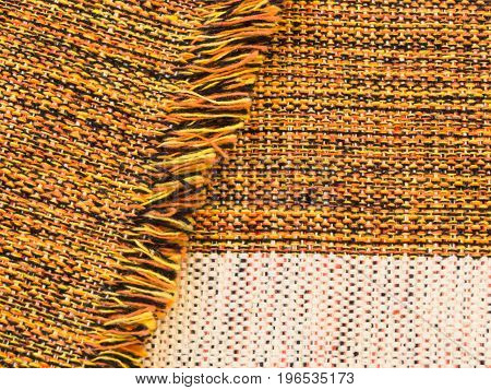 Close-up of handmade ruddy cotton fabric blended of orange, black, yellow and white, folded with fringes