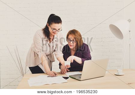 Two women in the office. Teamwork, business communication. Middle-aged architects designers in team work discuss project. Start up discussion. Female coworkers.