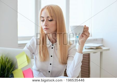 Young beautiful woman working behind laptop at office.