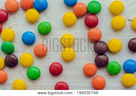 Colorful chocolate coated candies texture on white wooden background. Top view.