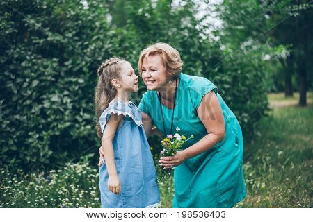 Grandmother playing with her granddaughter in summer park