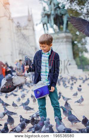 Cute boy with pigeon birds near Notre Dame de Paris cathedral in Paris, France