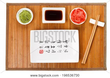 Set of sushi tablewear. Top view on empty rectangular sushi plate with hieroglyphs, saucer, ginger, wasabi and chopsticks on bamboo mat. Flat lay, copy space, background