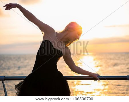 Beautiful ballerina performing pirouette. Blonde woman in black ballet tutu on embankment above ocean or sea beach at sunrise. Female dancing with arms.
