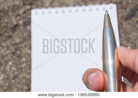 Open white note book on rings with metal ball pen in female's hand on the sandy beach