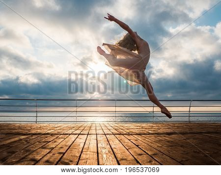 Jumping ballerina in beige dress and pointe on embankment above ocean or sea beach at sunrise.Beautiful blonde woman with long hair practicing stretching and classic exercises.Epic jump.