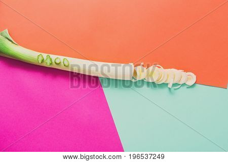 Cooking healthy food. Sliced and chopped leek on abstract colorful background, top view, copy space