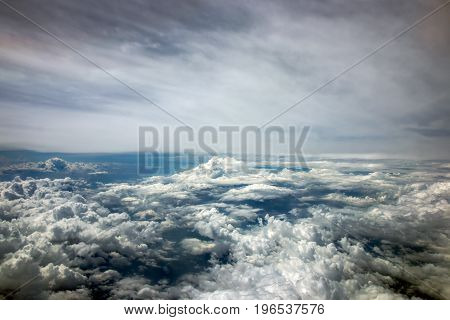 The dramatic sky with clouds made from a window of an airplane.