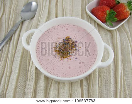 Red strawberry frothy soup with sugar flowers