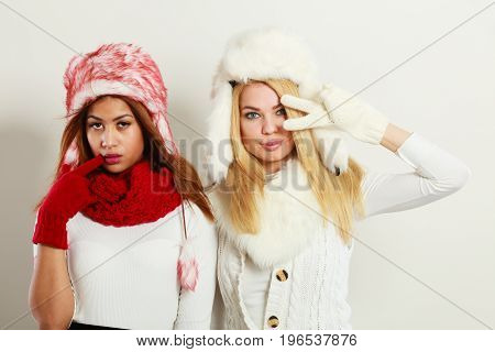 Fashion winter outfit concept. Two girls blonde and mulatto in warm red white clothing having fun. Attractive women wearing fur caps scarfs gloves.
