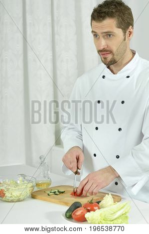 Portrait of a handsome young chief preparing vegetable salad