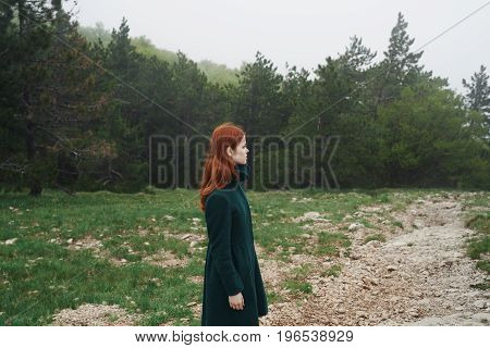 Young beautiful woman is walking in the mountains by the forest.