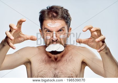 Young guy with a beard on a white isolated background, wadded disks, ear wax, cosmetic cream.