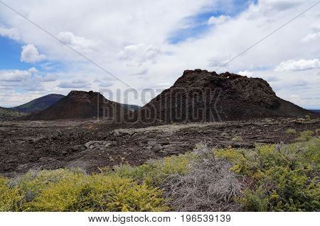 Two spatter cones and one cinder cone rising above a landscape of black volcanic basalt rock from eruptions along the Great Volcanic Rift Zone, a line of cones and lava vents. Craters of the Moon, USA