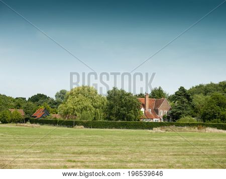 Country Farm House Behind Trees And Field